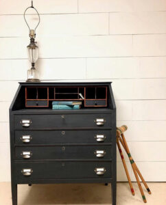 Picture of a black desk with croquet mallets leaning against the right side.