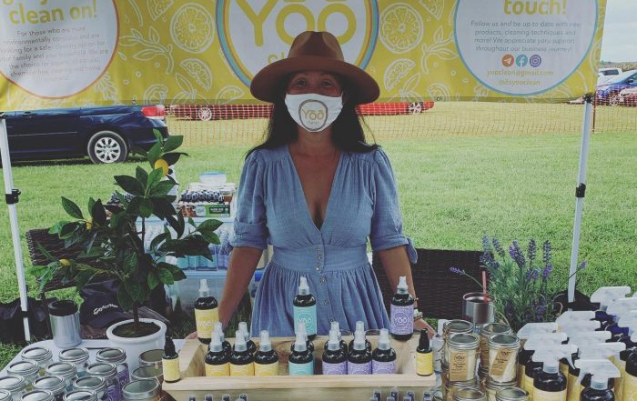 Yoo Clean owner standing in front of her products at a farmers market