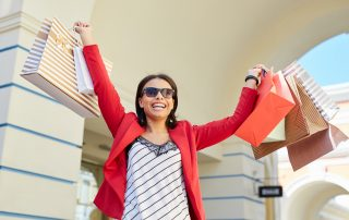 Jolly positive young black woman in sunglasses excited about shopping sales raising hands full of colorful paper bags outside